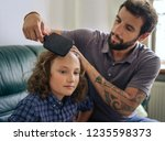 single dad using a brush to... | Shutterstock . vector #1235598373