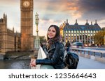 Small photo of Attractive, young, female London traveler tourist enjoys the view to the Westminster Palace and Big Ben clocktower touring a sightseeing city trip