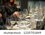 people tasting white wine... | Shutterstock . vector #1235701849