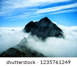 mountain rising from the fog ... | Shutterstock . vector #1235761249