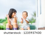 little sister playing with her... | Shutterstock . vector #1235937430