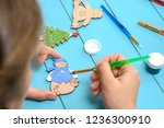 child draws on a wooden toy.... | Shutterstock . vector #1236300910