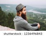 Portrait of a serious stylish bearded hipster sitting on a rock on a mountain side in the background of an epic landscape.