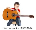 Sad white boy with a  acoustic guitar in his hands. The child does not want to be engaged in music  - isolated on white background - stock photo
