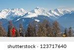 Skiers cruising down a ski run in the Alps. - stock photo