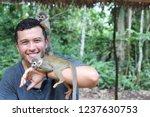 Stock photo handsome ethnic man with titi monkeys 1237630753