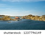 Sea landscape of rocky coastline on the South of Sweden. Southern coastline of Sweden with view at rocky islands. Red fishing houses on the shore.