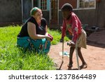 Small photo of Uganda. 2017/4/28. A white-skinned missionary medical doctor (called 'mzungu' or 'muzungu' by the locals) delights in the progress her patient - a young boy walking with crutches - is making.