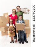 Happy family with two kids moving to a new house carrying their stuff - stock photo