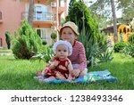boy sits as a baby girl on lawn ... | Shutterstock . vector #1238493346