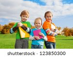 three kids standing with books... | Shutterstock . vector #123850300