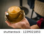 a cup of coffee in the hand of... | Shutterstock . vector #1239021853
