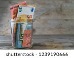 Euro Bills In A Glass Jar On A...