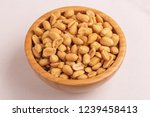roasted peanuts in wooden bowl... | Shutterstock . vector #1239458413