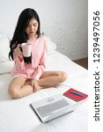 woman sitting on bed has cup of ... | Shutterstock . vector #1239497056