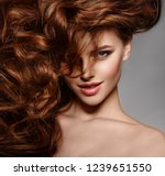 Stock photo beauty fashion model with long shiny hair waves curls volume hairstyle hair salon updo woman 1239651550