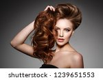 Stock photo beauty fashion model with long shiny hair waves curls volume hairstyle hair salon updo woman 1239651553