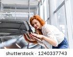 redhead girl inspects a new car ... | Shutterstock . vector #1240337743