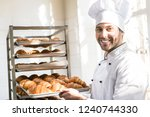 smiling baker holding tray with ...   Shutterstock . vector #1240744330