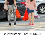 Small photo of Shenzhen, China - November 24 2018: women carrying groceries in various throw-away plastic shopping bags. Inconsiderate consumption of plastic bags is one of the big source of environment pollution