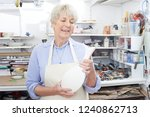 senior woman holding vase in... | Shutterstock . vector #1240862713