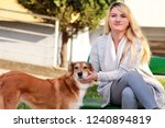 Stock photo beautiful girl with his shetland sheepdog dog sitting and posing in front of camera on wooden bench 1240894819
