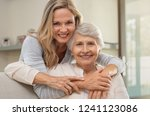 Stock photo cheerful mature woman embracing senior mother at home and looking at camera portrait of elderly 1241123086