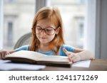 red haired little girl reading...   Shutterstock . vector #1241171269