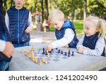 Small photo of The topic children learning, logical development, mind and math, miscalculation moves advance. large family brothers and sister Caucasian boys and girl playing chess park bright sunny weather autumn.