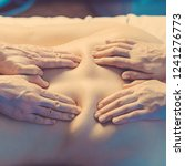Small photo of Concept of healthcare and female beauty. Toned image. Two masseuses make a double back massage of a girl in a spa salon. Four hands of the masseur view