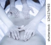 Small photo of Concept of healthcare and female beauty. Toned image. Two masseuses make a double back massage of a girl in a spa salon. Four hands of the masseur during the massage square view