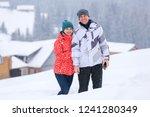 happy couple standing on snowy... | Shutterstock . vector #1241280349