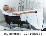young woman washing head with... | Shutterstock . vector #1241480836