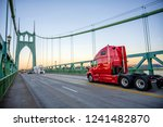 Bright red bonnet big rig semi truck tractor with high cab running on the St Johns Bridge with another traffic across Willamette river in industrial area of Portland to warehouse for pick up trailer