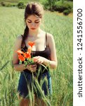 girl with red poppies on the... | Shutterstock . vector #1241556700