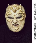 Small photo of Man with dragon skin and beard. Monster face with evil look of white eyes. Demon head on black background. Alien or reptilian makeup with sharp thorns and warts. Horror and fantasy concept.