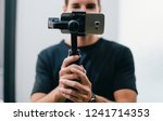 man holding a gimbal with a... | Shutterstock . vector #1241714353