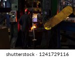 hot iron in smeltery held by a... | Shutterstock . vector #1241729116