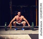tensing man lifting barbell in... | Shutterstock . vector #1241895190