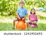boy and girl are jumping on a... | Shutterstock . vector #1241902693