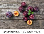 ripe plums on a rustic wooden... | Shutterstock . vector #1242047476