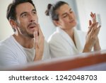 Small photo of Gorgeous couple going through daily beauty regime in bathroom