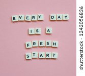 "Small photo of Quotes ""Every Day Is a Fresh Start"" on pink background."