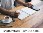 man's hand writing on paper... | Shutterstock . vector #1242114583