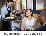 diligent  pleasant waiter with... | Shutterstock . vector #1242187666