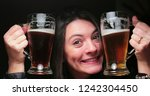 woman drinking beer from two... | Shutterstock . vector #1242304450