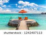 wooden sunbed and umbrella on...   Shutterstock . vector #1242407113
