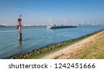 Small photo of Ship sailing on the New Waterway along industries and wind turbines in the direction of the North Sea. This is the access route for large seagoing vessels from the North Sea to the port of Rotterdam.