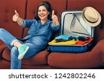 smiling woman sitting on sofa... | Shutterstock . vector #1242802246