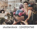 beautiful girl florist sends... | Shutterstock . vector #1242924760